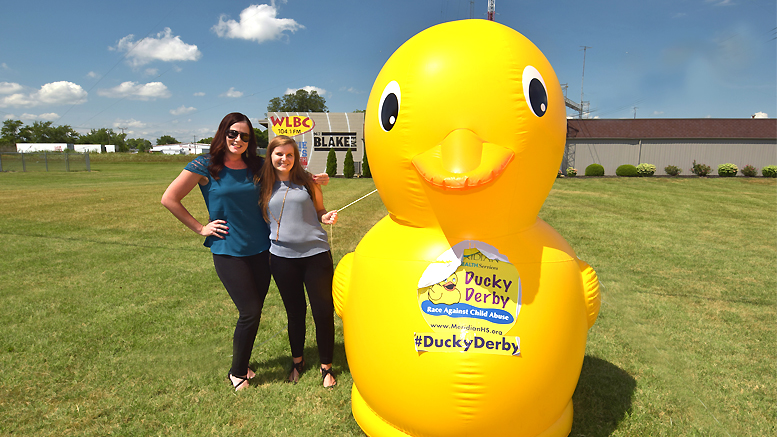 Lindsay Stafford and Liz Valpatic beside one of the 8 foot yellow ducks on the property of Woof Boom Radio. Photo by: Mike Rhodes