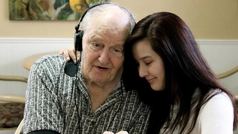 Athena Nagel, a Music & Memory volunteer, comforts Gene Hart, a Muncie Alzheimer's patient, during a therapeutic iPod music session. Photo provided.