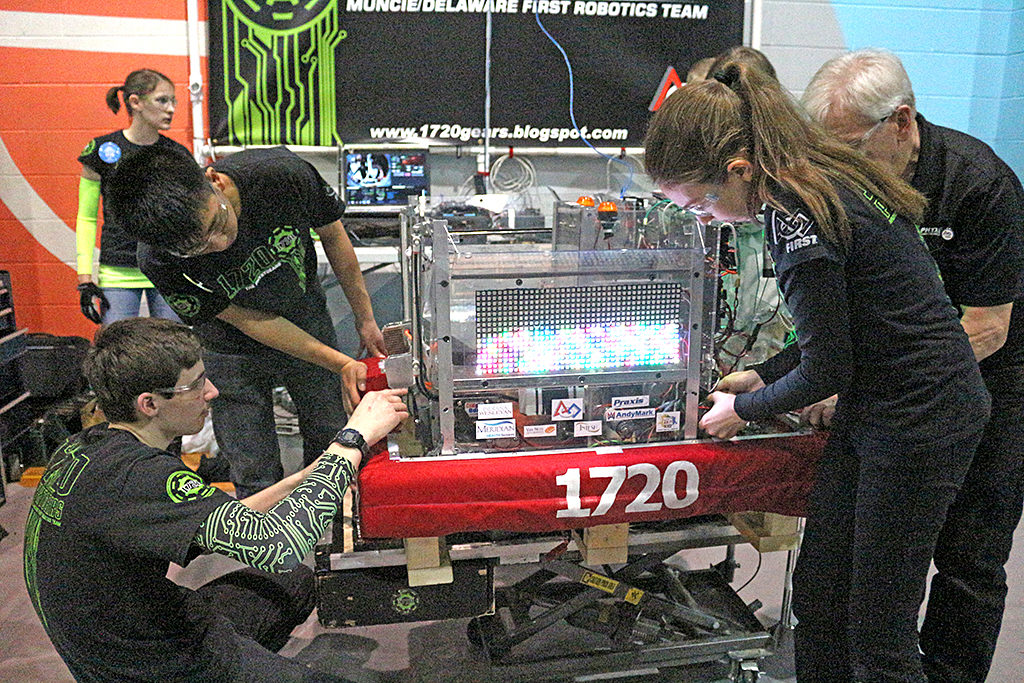 Team members working on the PhyXTGears robot in the pits. Photo includes Jessica Van Ness, Ethan Nguyen, John Pugsley, Moriah Schlenker and mentor, Mike Koch.