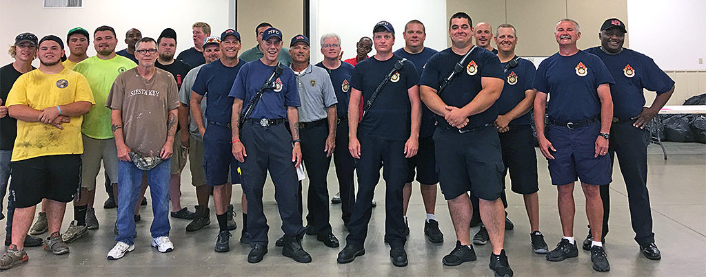 Volunteers from the City of Muncie Parks Department, Muncie Sanitary District and Muncie Fire Department are pictured after moving thousands of backpacks to the fairgrounds. Photo by: Kay Walker