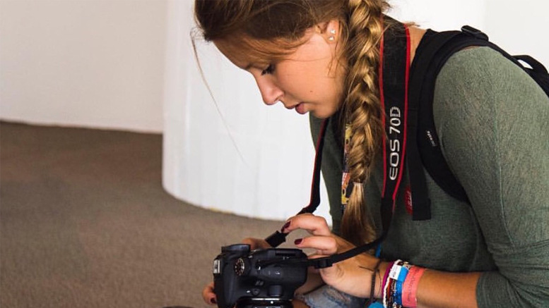 Grace Hollars, Ball State '19, examines her camera while participating in the university's immersive learning experience BSU at the Games in Rio in 2016. Hollars is returning to the Olympics through BSU at the Games this winter to cover the 2018 Games in South Korea. Photo provided
