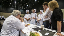 Culinary Arts students present their entry as a judge for the culinary competition listens to their presentation. Photo by: Mike Rhodes