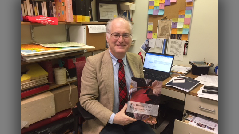 "Ball State history professor Ron Morris is pictured with his new book, ""The History of Indiana State Forests."" Photo provided."