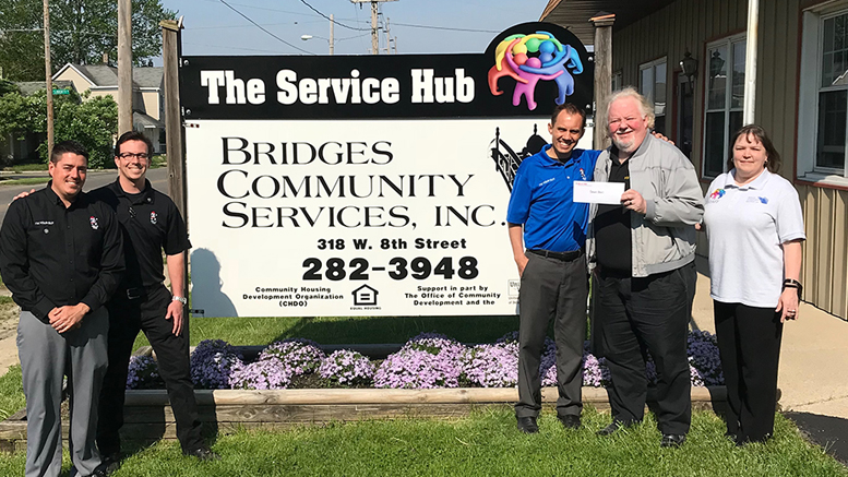 Belle Tire representatives present a check to Bridges Community Services. Photo provided.