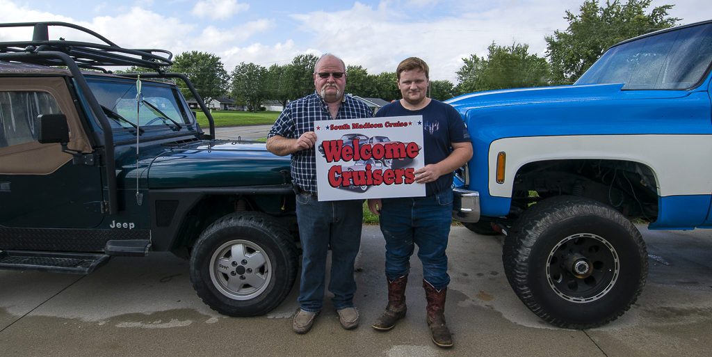 Troy Watters and son Nick Watters are pictured by their favorite Jeep and '79 GMC High Sierra Square Body truck. The sign they are holding appears by South Madison Street businesses who encourage participants to pull into their parking lots. Photo by: Mike Rhodes