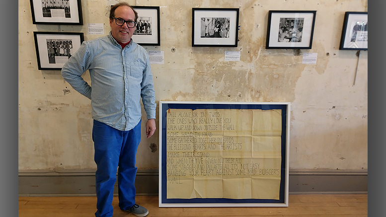 "Mark Perretta stands beside the 40""x50"" mount and frame he crafted surrounding lyrics handwritten by Roger Waters of Pink Floyd. Photo provided"