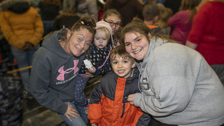 A family poses for a picture during the 25th annual Tiny Adams Memorial Christmas event held at fire station #1 in downtown Muncie. Photo by: Mike Rhodes