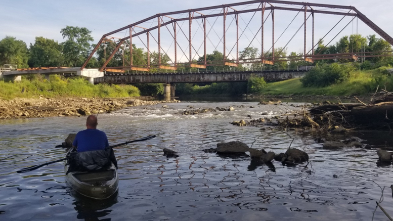 Angler fishing for small mouth bass below the Kitselman Bridge at the rediscovered limestone outcropping the day after the Indiana Steel and Wire Dam was removed. Photo provided
