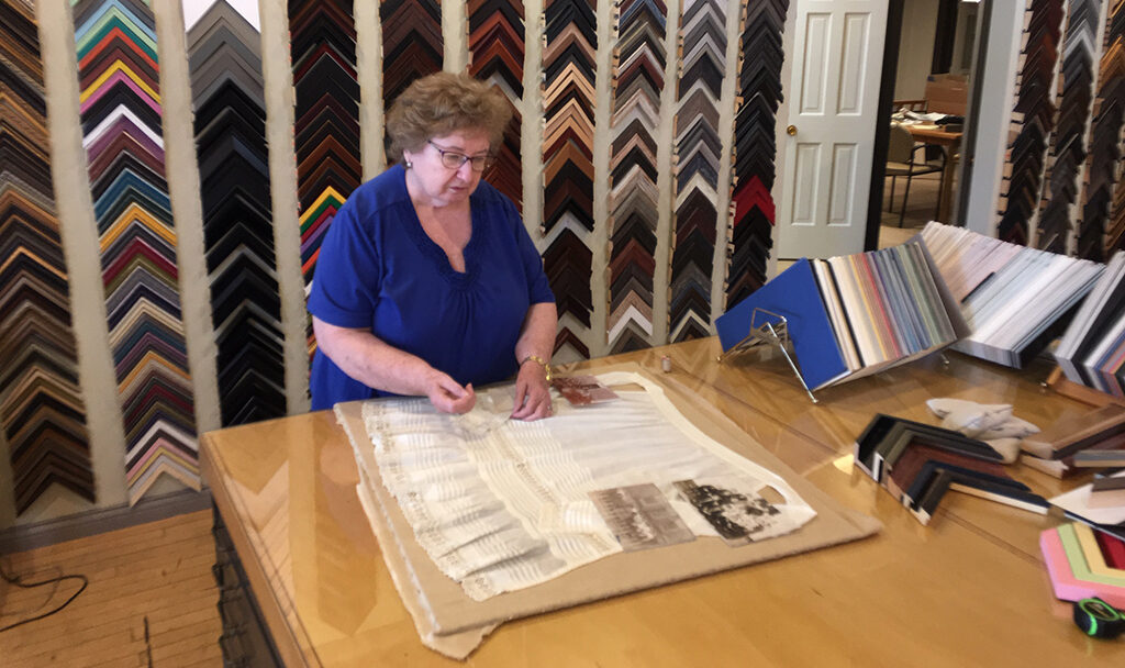 Rosie Sampley works on an early 20th century apron worn by a Pennsylvania teacher and now being framed and preserved by her family. Rosie has over thirty years of framing experience. Photo provided