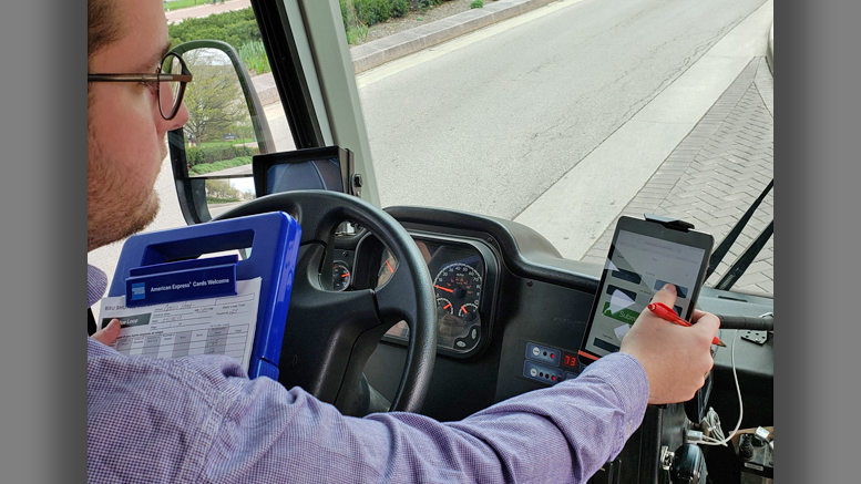 A BSU bus driver is pictured utilizing a new digital tracking system developed by a Capstone Connector team of students. On the left, the driver is holding a blue tablet that utilized an older manual paper entry method. Photo courtesy of Huseyin Ergin