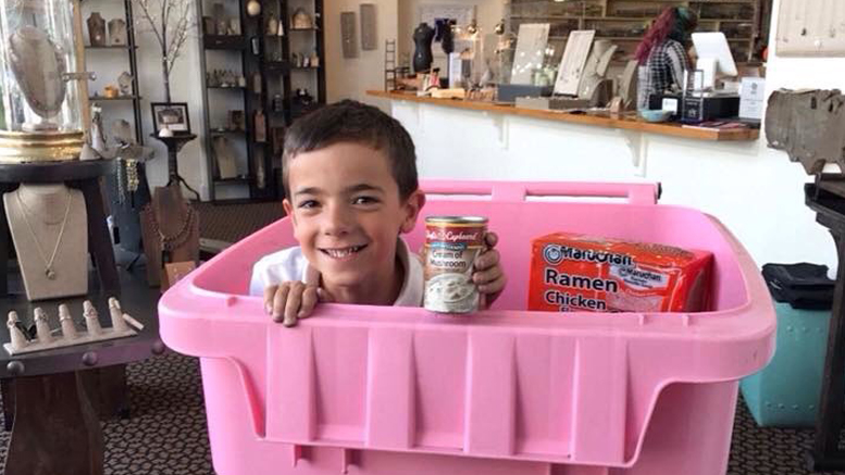 Adam Hale is pictured inside a Feed My Sheep donation container at the offices of Heidi J Hale Designs on Walnut Street in downtown Muncie. Photo provided