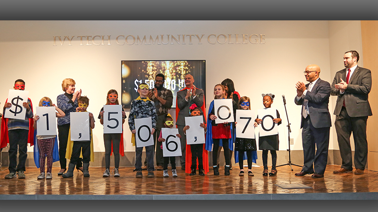 Campaign co-chairs Liz Ludwick and Damon Elmore reveal the dollars raised. Photo by: Lorri Markum
